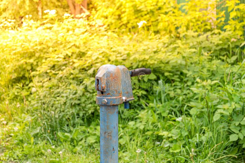 Vintage rusty water fountain hand pump in russian village. Abandoned water wellhead royalty free stock images