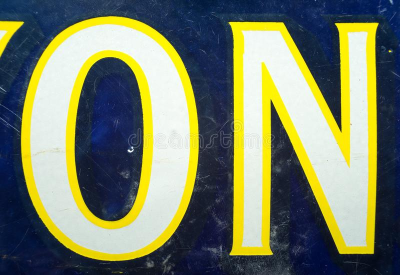 Vintage 1930s weathered enamel ON text on an enamelled sign in blue, yellow and white. Potential use as NO sign if rotated stock photos