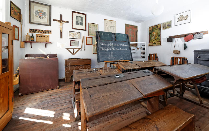 Vintage school classroom. With period furniture comprising seats and desks, blackboard, pictures, cross and bookcase stock photo