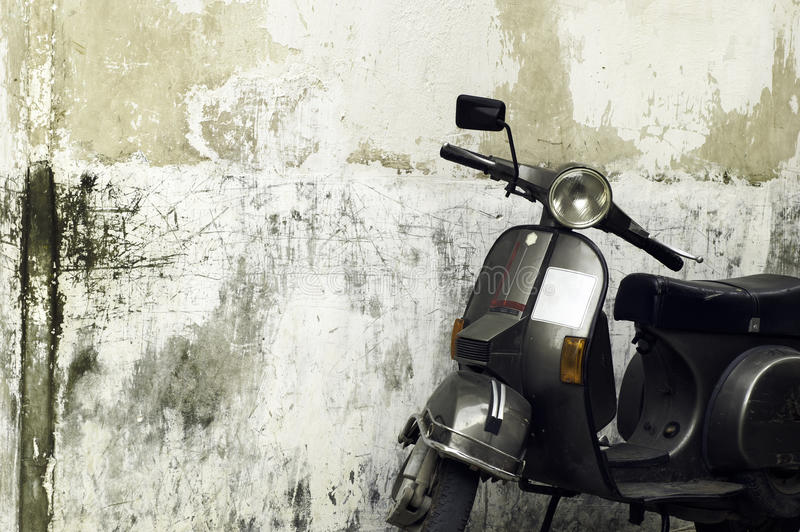 Vintage scooter. Motorised scooter parked in front of a grungy wall royalty free stock photos