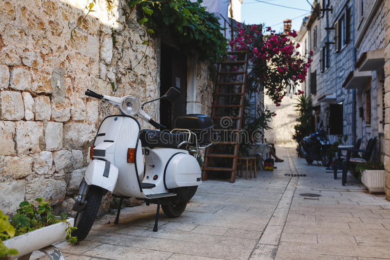 Vintage scooter parked in a narrow street in croatia. Vintage scooter parked in a typical narrow old street in croatia royalty free stock photos