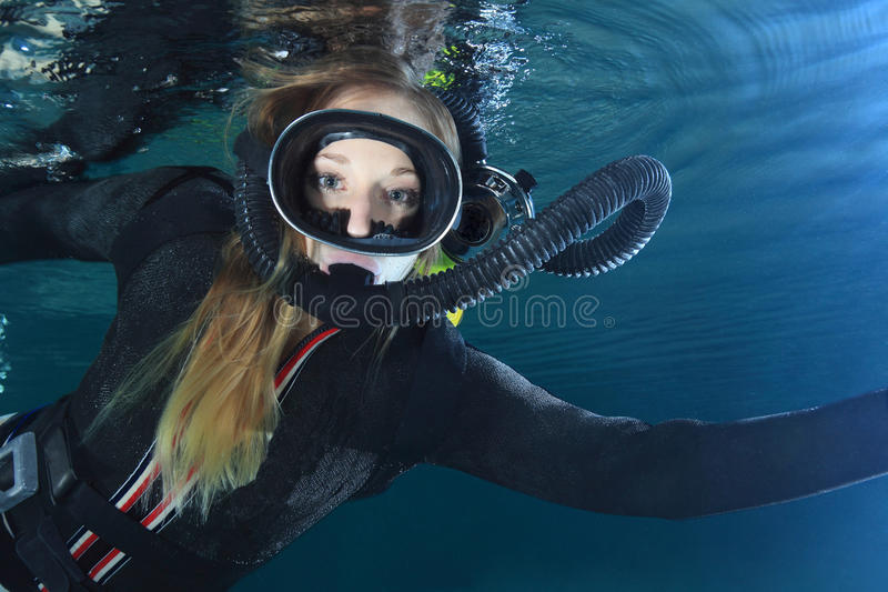 Vintage scuba woman. Scuba woman with black neoprene dress diving underwater stock images