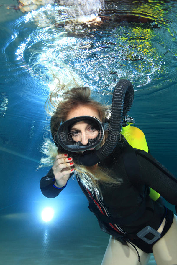 Vintage scuba woman. Scuba woman with black neoprene dress diving underwater stock photos