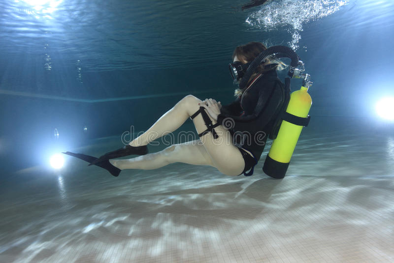 Vintage scuba woman. Scuba woman with black neoprene dress diving underwater royalty free stock images