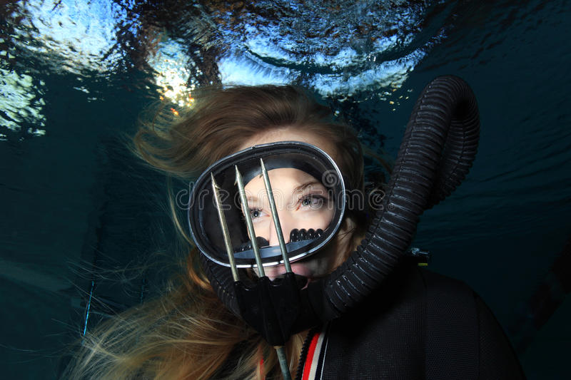 Vintage scuba woman. Scuba woman with black neoprene dress and spear gun diving underwater royalty free stock photo