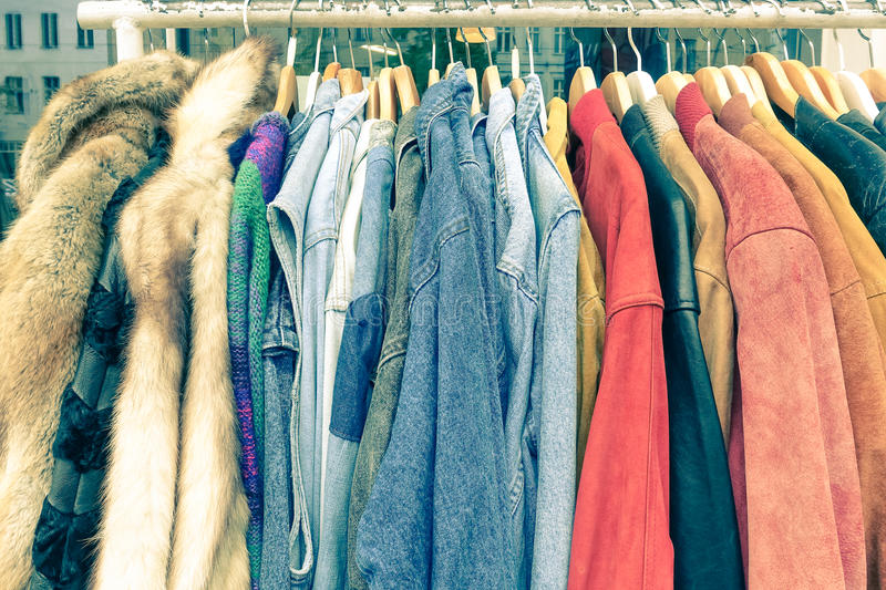 Vintage second hand clothes hanging on shop rack at flea market. Vintage second hand clothes hanging on shop rack at weekly flea market - Hipster wardrobe sale royalty free stock photos