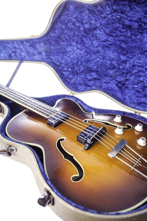 Vintage semi-acoustic bass guitar. A vintage semi-acoustic archtop bass guitar with sunburst finish in original tweed case stock photos