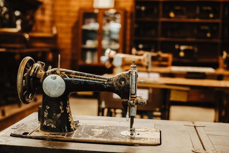 Vintage sewing machine in workplace of garment factory. Retro technology. vintage color tone stock images