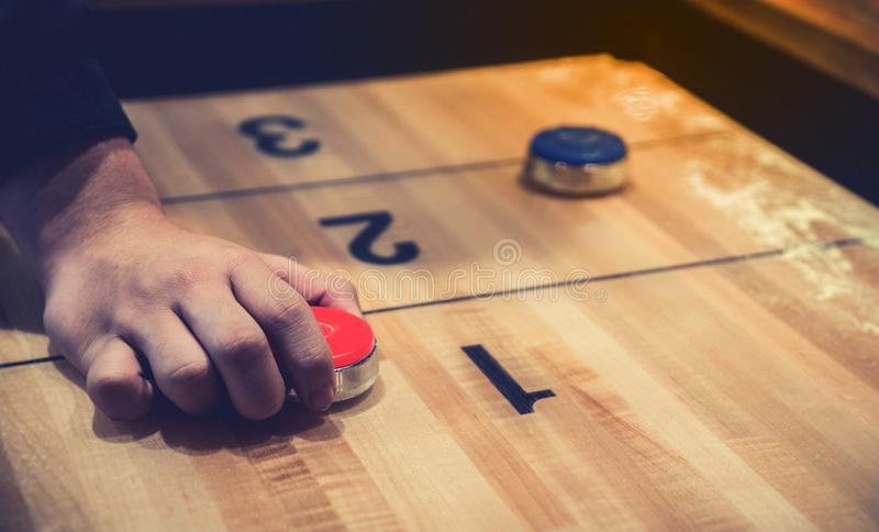 Vintage shuffle board game with red and blue disc and hand holding red blue disc on wooden shuffle table. Shuffleboard table game royalty free stock images