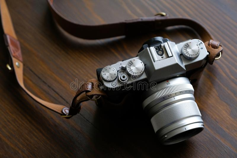 Vintage silver and black camera with brown leather strap on wooden table royalty free stock photography