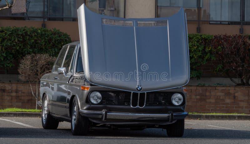 Старинный серебристый BMW с поднятым капотом. BMW 2002 at a car meet with hood raised on a sunny day стоковые изображения