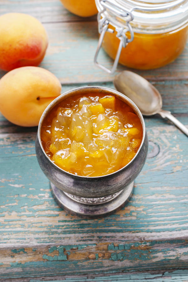 Vintage silver goblet of peach jam. Standing on a rustic wooden table royalty free stock photo