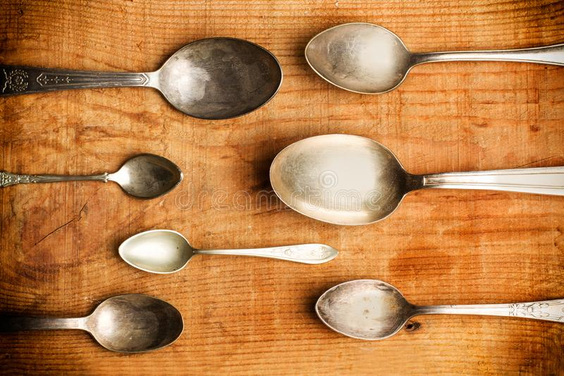 Vintage silver spoons on a rustic table stock image