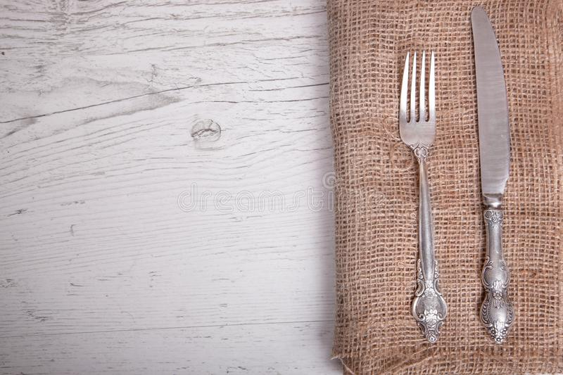 Vintage silver tableware knife and fork is on napkin, on an old stock image