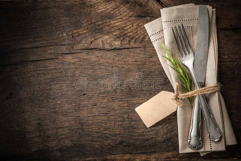 Vintage silverware with an empty tag. Vintage silverware with a twig of rosemary and empty tag on rustic wooden background stock image