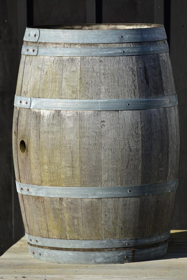 Vintage wooden slate barrel. Vintage slate wooden barrel with bit weathered staves surface and galvanized hoops and cylindrical hole in middle where diameter is stock photo
