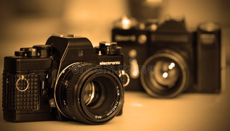 Vintage SLR cameras. Two vintage SLR cameras in sepia colour stock image