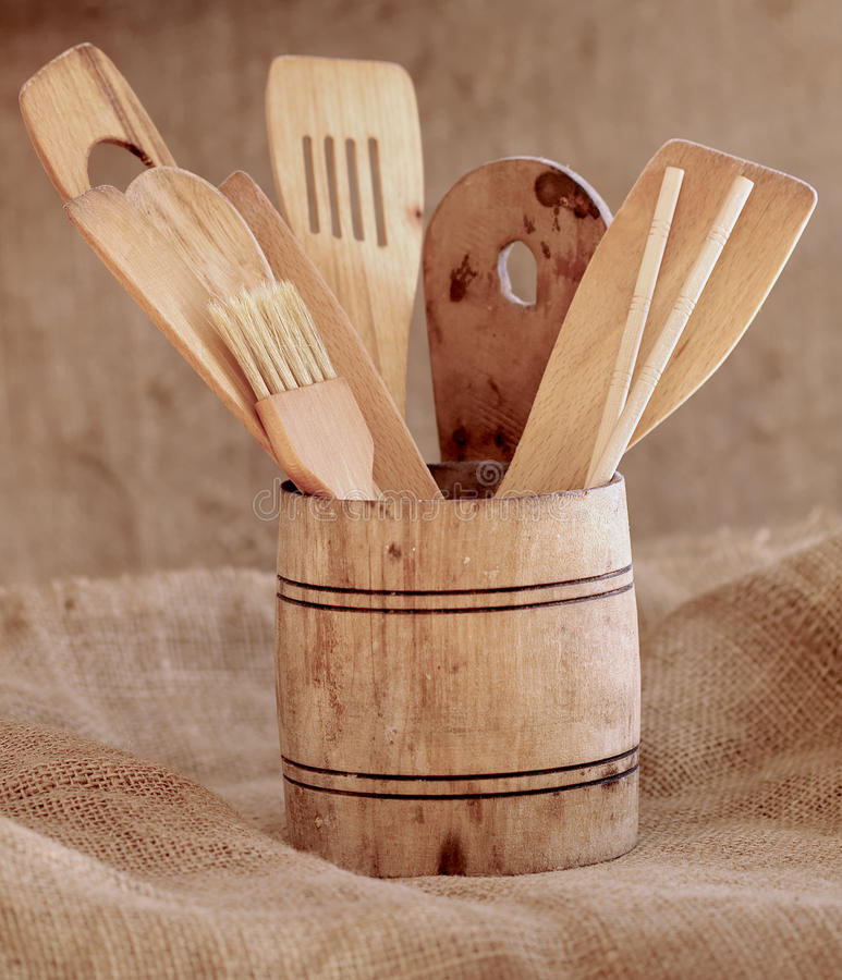 Vintage small wooden bucket with various kitchen utensils. On a rustic background royalty free stock photo