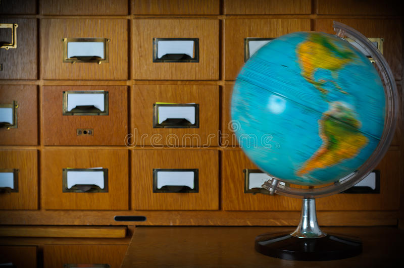 Vintage Spinning Globe in front of old Library Card Catalogue stock photo