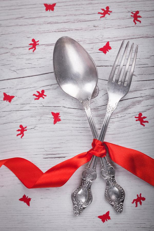 Vintage spoon and fork with a red tape, angels and butterflies for Valentine`s day on a wooden royalty free stock photo