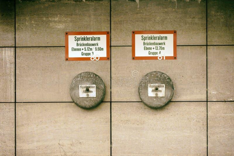 Vintage sprinkler. The alarm bells of a sprinkler system with signs on a wall stock image