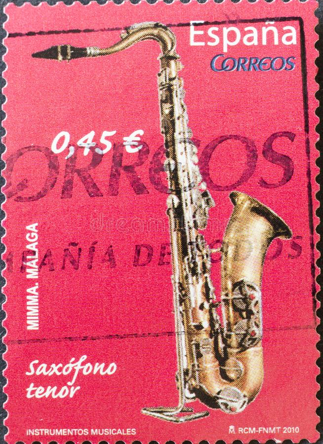 Vintage stamp printed in Spain shows saxophone royalty free stock photo