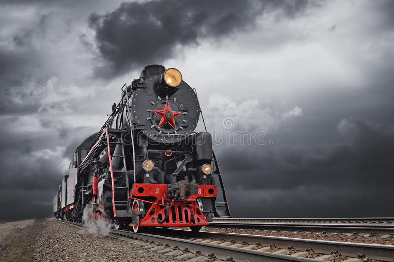 Vintage steam train in motion. Steam engine and carriages, in full steam royalty free stock photography