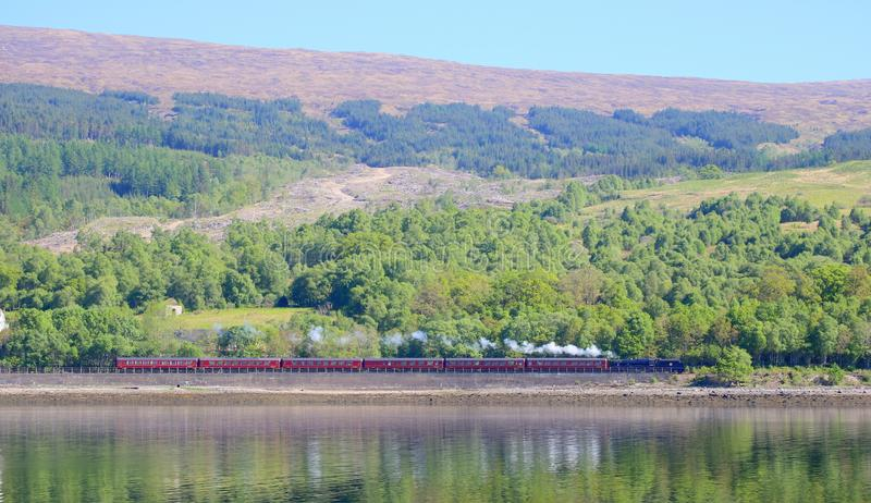 Vintage steam train steaming by lake. A vintage steam train running by Loch Eil in the Highlands of Scotland stock photography