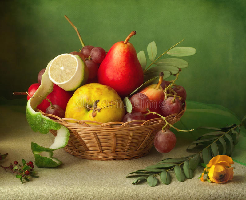 Vintage still life with basket of fruits over blur background royalty free stock images