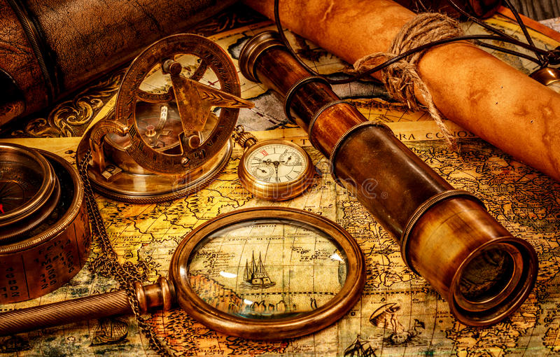 Vintage still life. Vintage magnifying glass, compass, telescope and a pocket watch lying on an old map