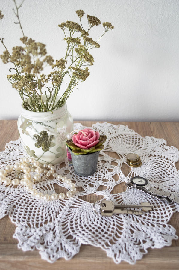 Vintage still life with necklace, keys, watches, candle and vase with flowers on doily stock photography