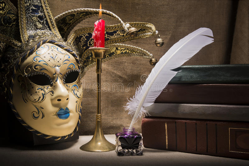 Vintage still life with old books near inkstand, feather, venezian mask and burning red candle in candlestick on canvas background stock image