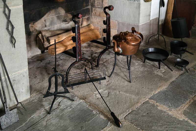 Vintage stone fireplace  with metal tools and fire wood. Vintage design mantelpiece stock images