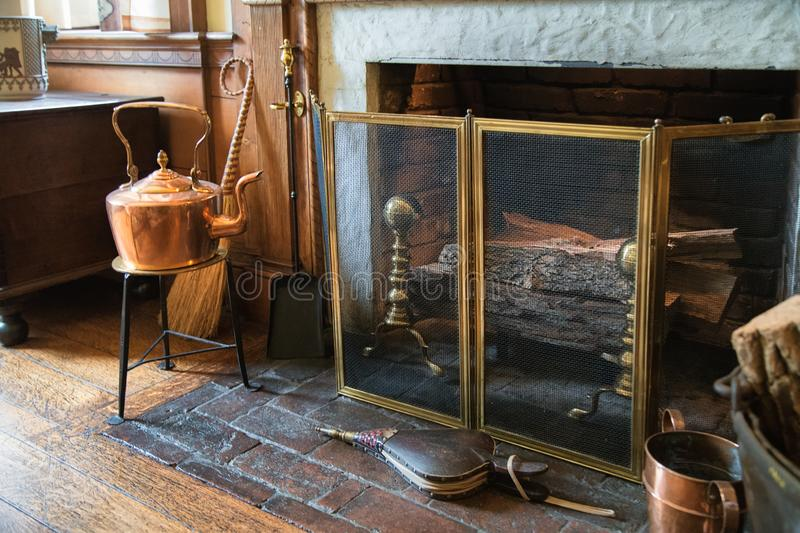 Vintage stone fireplace  with metal tools and fire wood. stock photo