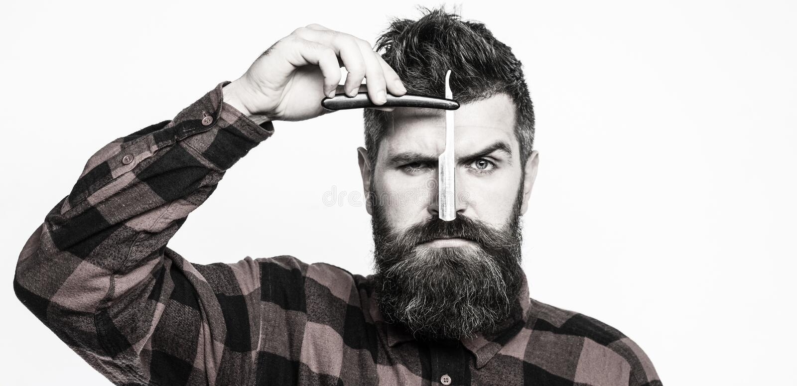 Vintage straight razor. Barbershop service concept. Handsome bearded hairdresser is holding a straight razor while royalty free stock photo