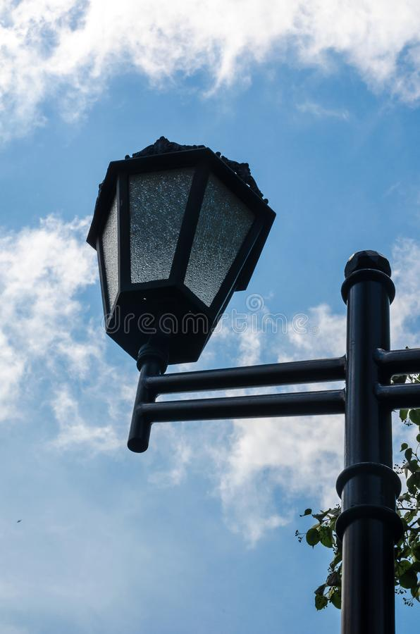 Vintage street lamp on a background of summer blue sky. Clear lines and soft clouds. Down up royalty free stock image