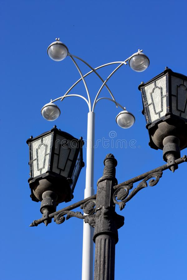 Vintage street lamp and modern lantern against a blue sky stock image