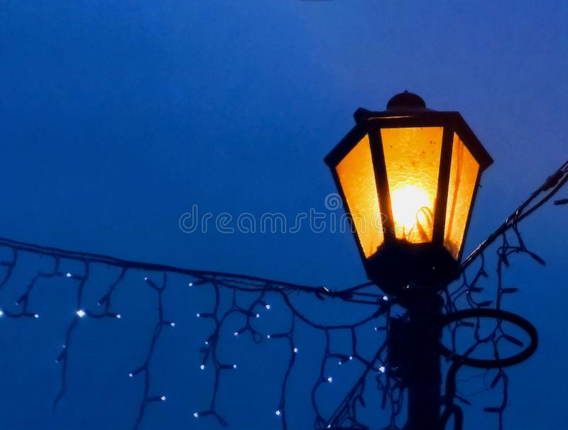 Vintage street lamp on a night background with a blur effect. Closeup. royalty free stock image