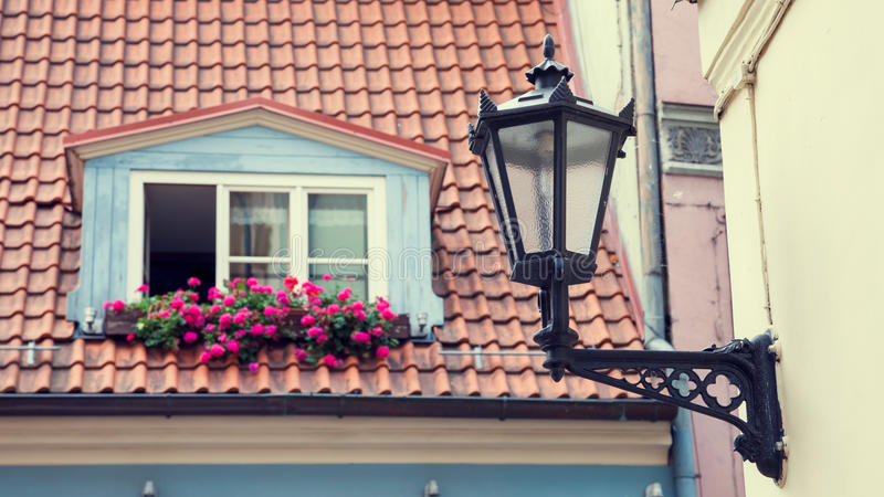 Vintage street lamp on wall and window in garret roof. On background. Selective focus royalty free stock images