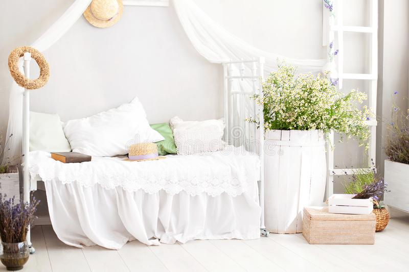 Vintage studio apartment interior in light colors in old style. Shabby white chic bedroom interior for a country house. Interior i. Tems in Provence. bouquet of royalty free stock photo