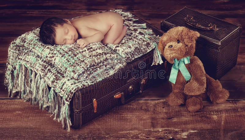Vintage style baby. A studio vintage photo of a newborn baby sleeping on top of a luggage royalty free stock photo