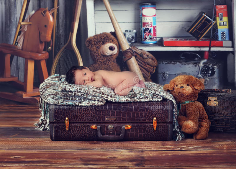 Vintage style baby. A studio vintage photo of a newborn baby sleeping on top of a luggage stock photo