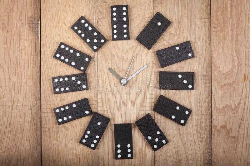 Vintage style clock made of domino plates on wooden background. Domino clock royalty free stock image