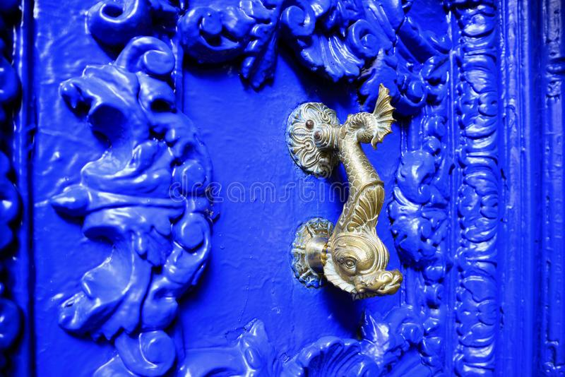 Vintage style dolphin shaped brass door knocker on vivid blue carved wood door, Cuzco, Peru. Background royalty free stock images