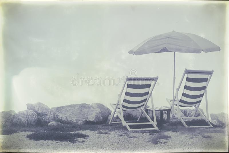 Vintage style filtered image of two empty beach chairs and umbrella on coastline royalty free stock photos