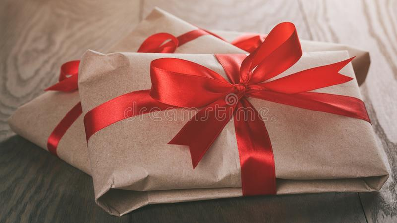 Vintage style gifts tied with ribbon and bow. On old oak table royalty free stock photos