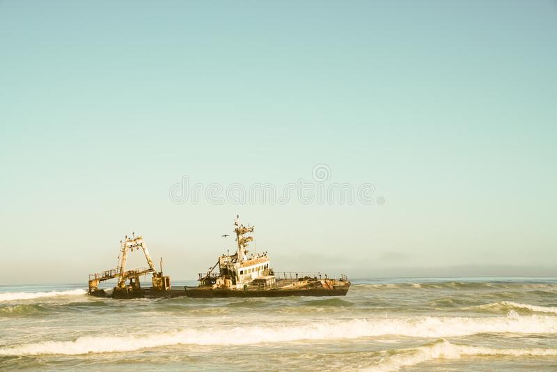 Abandoned shipwreck on Skeleton Coast, Namibia. Vintage style image of abandoned shipwreck on Skeleton Coast, Namibia royalty free stock image