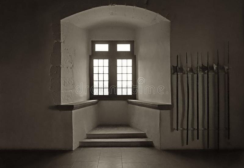 Warrior Room in Castle with Battle Axes and Window. A vintage style image of a deeply recessed window alcove in the Chateau Grandson with a display of the royalty free stock photos