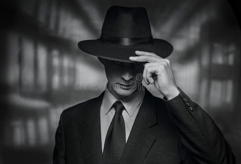 Vintage style image of a polite young man. The detective takes on the camera. Vintage style black and white image of a polite young man in a suit doffing his hat royalty free stock photography