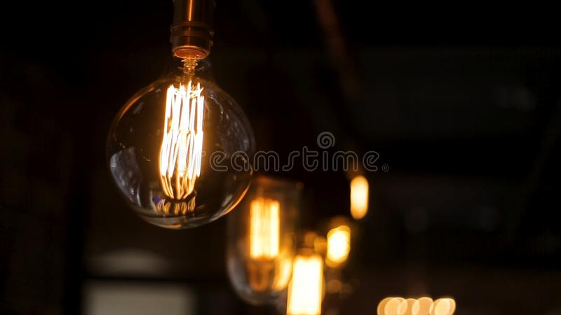 Vintage style light bulbs hang and decorated in a living room. Retro luxury light lamp decor glowing.The light from the royalty free stock photo